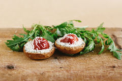 Delicious fresh canape with gorgonzola parmezan and strawberry a. Nd arugula on wooden desk on craft background Stock Images