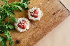 Delicious fresh canape with gorgonzola parmezan and strawberry a. Nd arugula on wooden desk, top view Stock Images