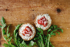 Delicious fresh canape with gorgonzola parmezan and strawberry a. Nd arugula on wooden desk, top view Royalty Free Stock Photography