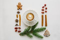 Delicious fresh cappuccino coffee in a mug with a flower pattern. Nearby various elements of Christmas or winter theme.  stock photography