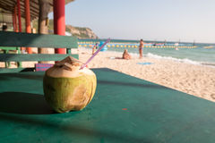 A delicious fresh coconut drink on the green table. Fresh and cold coconut drink from a tree near the beach which I can see a beautiful view of Koh Lan, famous stock images