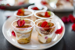 Delicious fresh cold strawberry cheese cake, dessert in plastic cups with rose petals on a dark background. Copy space Stock Photography