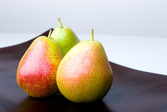 Delicious fresh colorful pears in a wooden vase Royalty Free Stock Image