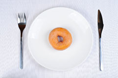 Delicious and fresh donut for breakfast. On a plate, with fork and knife Stock Photos