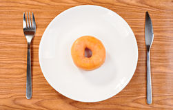 Delicious and fresh donut for breakfast. On a plate, with fork and knife Stock Images