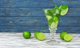 Delicious fresh drink cocktail mojito. From lime and mint with ice in a beautiful glass on a wooden background Stock Images