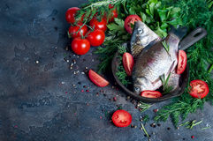 Delicious fresh fish on dark vintage background. Fish with aromatic herbs, spices and vegetables - healthy food, diet or cooking concept Stock Image