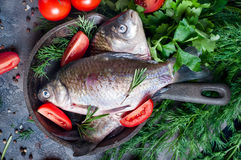 Delicious fresh fish on dark vintage background. Fish with aromatic herbs, spices and vegetables - healthy food, diet or cooking concept Stock Photo