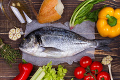 Delicious fresh fish and vegetables on dark vintage background. Royalty Free Stock Photo