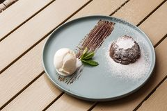 Delicious fresh fondant with hot chocolate and ice cream and mint served on plate. Lava cake recipe. Wooden background. Delicious fresh fondant with hot royalty free stock photography