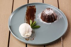 Delicious fresh fondant with hot chocolate and ice cream and mint served on plate. Lava cake recipe. Wooden background. Delicious fresh fondant with hot royalty free stock image