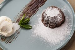 Delicious fresh fondant with hot chocolate and ice cream and mint served on plate. Lava cake recipe. Wooden background. Delicious fresh fondant with hot stock photography