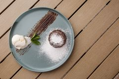 Delicious fresh fondant with hot chocolate and ice cream and mint served on plate. Lava cake recipe. Wooden background. Delicious fresh fondant with hot stock image