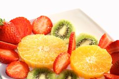 Delicious Fresh Fruits. Delicious slices of fresh fruits arranged on a white plate with white background. It's dessert time Stock Photo