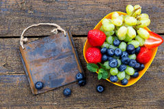 Delicious fresh fruits on a wooden table, rusty metal sign Stock Photos