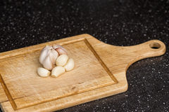 Delicious fresh garlic on wooden table in kitchen. Delicious fresh fresh garlic on wooden table in kitchen Royalty Free Stock Photography