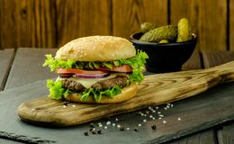 Delicious fresh homemade burger on a cutting board stock image