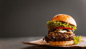 Delicious fresh homemade burger on a wooden table. Black background Royalty Free Stock Image