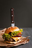 Delicious fresh homemade burger on a wooden table. Black background Stock Photos