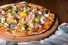 Delicious fresh homemade pizza with onions, vegetables and cheese on a wooden table. Copy space. close-up.  Stock Image