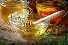 Delicious fresh honey and a Cup of healthy tea with lemon and rose hips on a wooden table. Selective focus. Royalty Free Stock Images