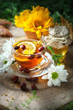 Delicious fresh honey and a Cup of healthy tea with lemon and rose hips on a wooden table. Selective focus. Stock Photo