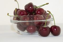 Fresh cherries in a bowl on the table. Delicious and fresh, juicy and sweet summer fruit. Red cherries in a glass bowl Royalty Free Stock Photo