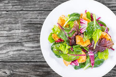 Delicious fresh low-calories salad of chicken breast and  lettuce leaves. Baby spinach, swiss chard, radicchio rosso in the white dish on the old wooden table Stock Photo