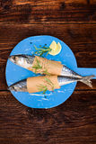 Delicious fresh mackerel fish on wooden kitchen board. Delicious fresh mackerel fish on wooden kitchen board with lemon, rosemary and salt flakes on brown Royalty Free Stock Photo