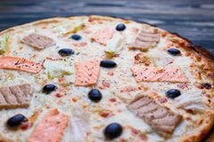Delicious fresh mediterranean fish pizza with salmon, tuna and o royalty free stock images