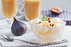 A delicious fresh melon and fig smoothie in a glass with a slice. Of fig on the white wooden background. Healthy food concept Royalty Free Stock Photo