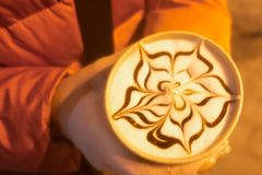 Delicious fresh morning cappuccino coffee with flower drawn on its milk foam, white chocolate cookies on the side and a big bunch royalty free stock images