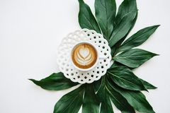 Delicious fresh morning cappuccino coffee in a mug with a flower pattern. Nearby lie the leaves of the plant for Royalty Free Stock Photo