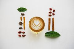 Delicious fresh morning cappuccino coffee in a mug on a white surface. Nearby are various ingredients Stock Image