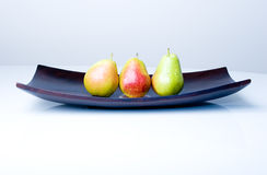 Delicious fresh pears in a wooden vase on a table. Three delicious fresh colorful pears in a wooden vase on the table royalty free stock images