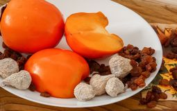 Delicious fresh persimmon fruit , raisins and dried figs on the plate and wooden table stock photos