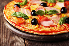 Delicious fresh pizza on brown wooden background. Stock Photo