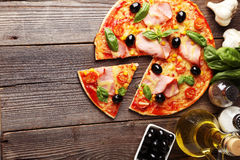 Delicious fresh pizza on brown wooden background Royalty Free Stock Images