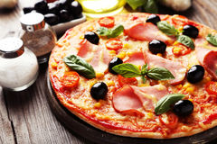 Delicious fresh pizza on brown wooden background Stock Image