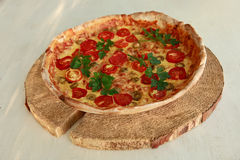 Delicious fresh pizza served on wooden plate Royalty Free Stock Images