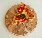 Delicious fresh pizza served on wooden plate Royalty Free Stock Photos
