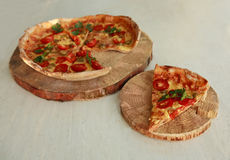 Delicious fresh pizza served on wooden plate Stock Image