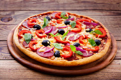 Delicious fresh pizza served on wooden table. Royalty Free Stock Images