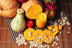 Delicious fresh pumpkin juice with the seeds in the Studio on wooden background . Smoothies on Halloween. Delicious fresh pumpkin juice with the seeds in the royalty free stock images