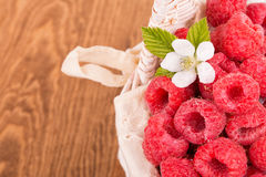 Delicious, fresh raspberries in a basket. With a flower and leaves, on wooden table Royalty Free Stock Image