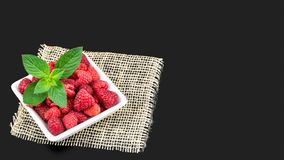 Delicious fresh raspberries on a dark gray background. Juicy red fruits in white square bowl with peppermint and decorative mat Royalty Free Stock Photography