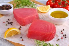 Delicious Fresh raw tuna fish steaks. Close-up of delicious Fresh raw tuna fish steaks prepared for cooking on cutting board with thyme leaves, lemon slices Royalty Free Stock Images