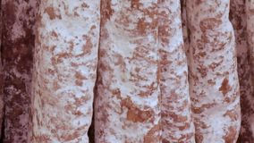 Delicious fresh salami sausages hang on the meat butcher market counter close up stock video footage