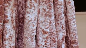Delicious fresh salami sausages hang on the meat butcher market counter close up stock video