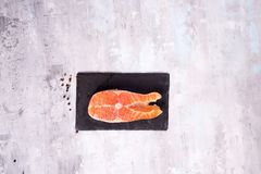 Raw salmon filet on dark slate cutting board. Lean proteins. Delicious fresh salmon fish on stone cutting board. Lean proteins Royalty Free Stock Photography